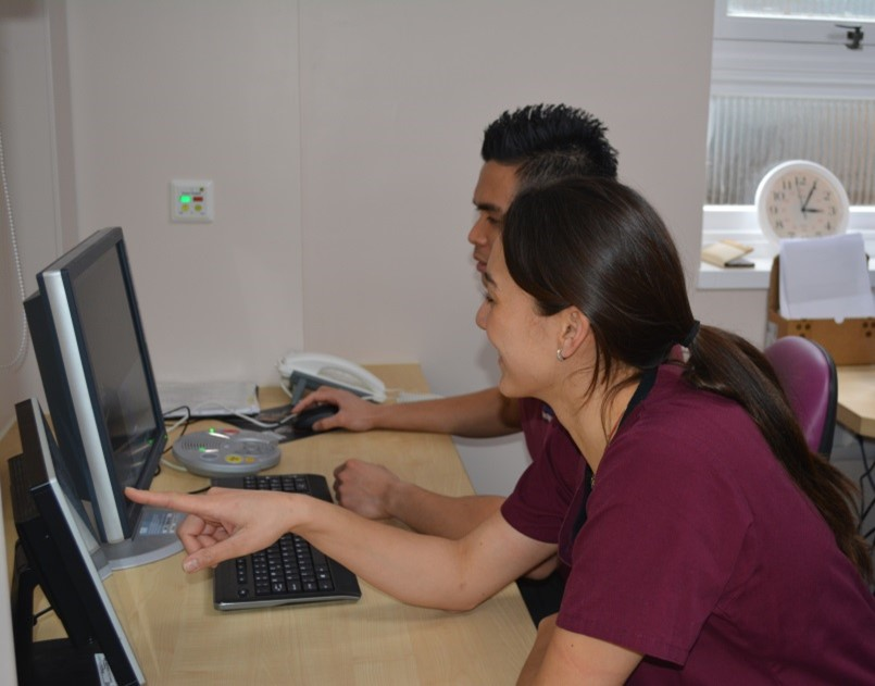 Two members of staff working on a computer